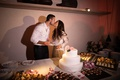 bride and groom kiss behind their small three-tiered wedding cake after cutting it