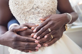 African American bride with pink manicure and rhinestone decals, yellow gold men's wedding band