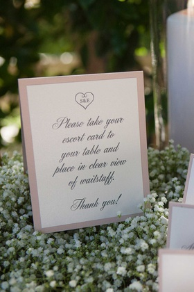 sign with instructions about escort cards on bed of baby's breath