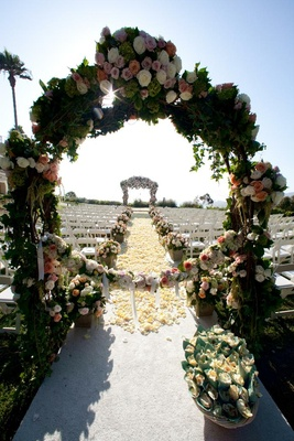 Outdoor wedding ceremony with flower archway