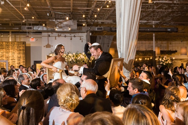 couple in hora chair dance jewish wedding