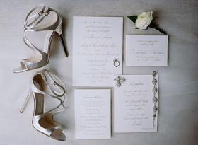 wedding invitation with gold calligraphy wedding jewelry and silver jimmy choo wedding heels