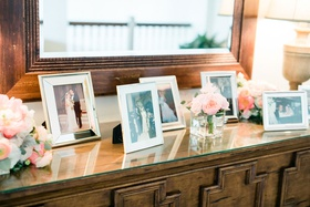 wedding reception credenza buffet table with family photos in frames mirror pink flowers lamps