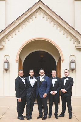 Groom in navy blue tuxedo jacket with white bow tie and groomsmen in black tuxedos bow ties