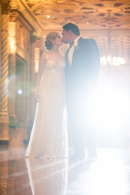 Bride in a beaded high-waisted Jenny Packham dress and updo kisses groom in black tuxedo