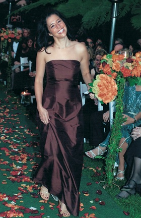 bridesmaid wears satin brown dress and carries orange roses bouquet