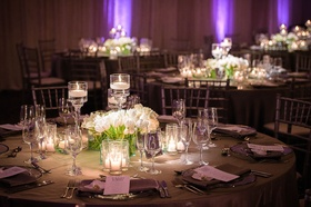 Wedding reception round table white flowers tall floating candles purple lights grey linens