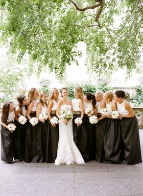 bride in vera wang gown, bridesmaids in long black skirts, white silk tops, leather belts