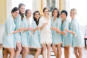 bride bridesmaids white blue robes getting ready classic southern wedding drinks mimosas morning of
