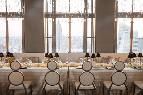Round circle chairs in triangle shapes with bench long table in front of windows with view of NYC