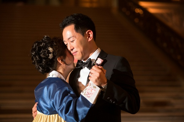 Korean mother in hanbok with blue bodice, gold skirt dances with groom in black tux at wedding