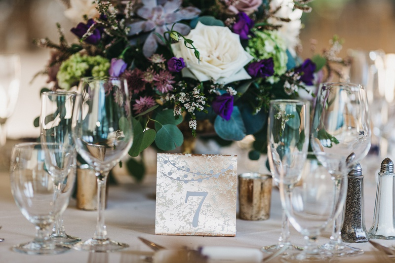 paper table number made to look like mercury glass in front of purple floral centerpiece