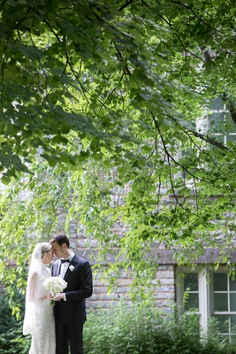 wedding portrait under green tree in front of historic building bride in veil high neck lace dress