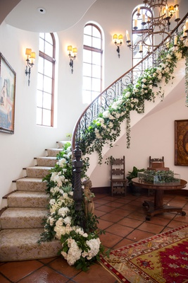 wedding reception at bride family home staircase with iron railing greenery white flowers
