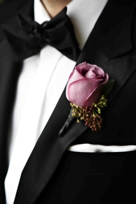 Groom wearing lavender pink rose on tuxedo lapel
