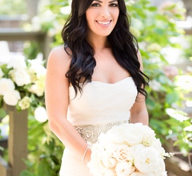 bride in vera wang and wavy hair holds garden rose white bouquet