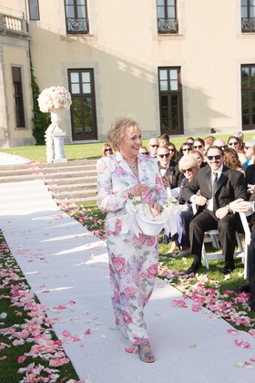 Grandma walking down white aisle runner at Oheka Castle in flower print dress with matching jacket