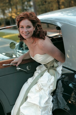 Bride in strapless wedding dress getting out of classic wedding car