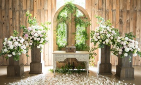 rustic-chic barn wedding ceremony, floral arrangements on wooden stand, gate with greenery