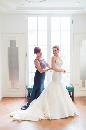 Bride in trumpet wedding dress with mother of bride helping button in navy dress with beaded bodice