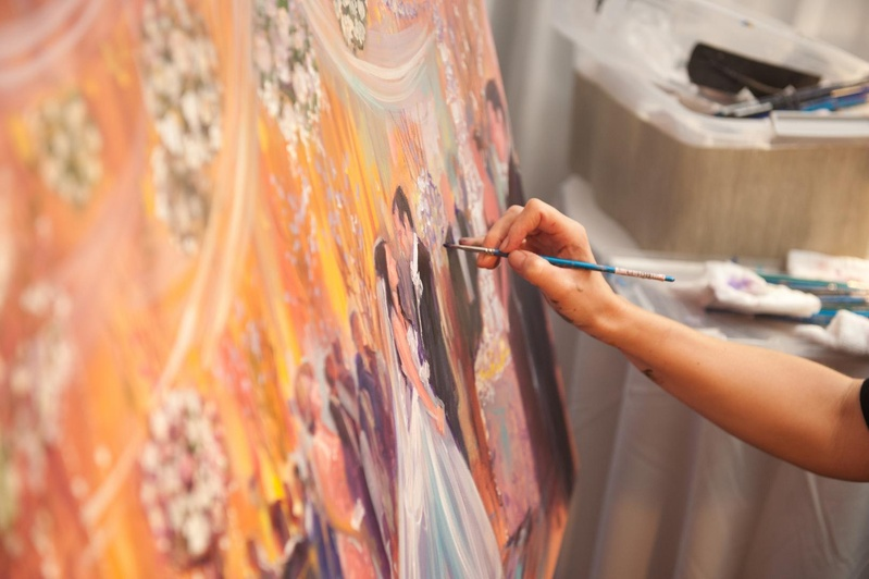 Artist painting scene of wedding reception on canvas