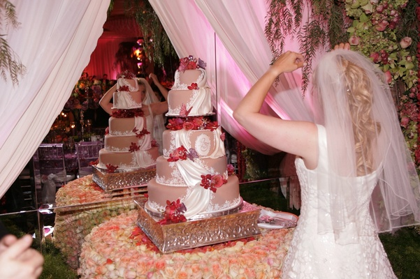 Five-tier pink wedding cake decorated with fondant draping, red butterflies and roses