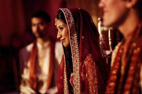 Indian wedding bride at ceremony with red and gold attire