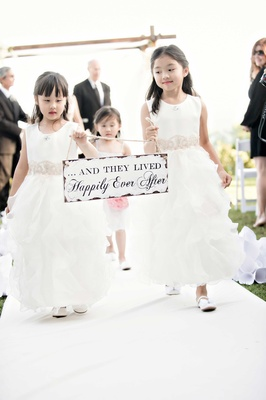 flower girls carrying sign up the aisle end of ceremony cute fairy tale saying outdoor california