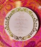 White and gold circular menu card on silk linens