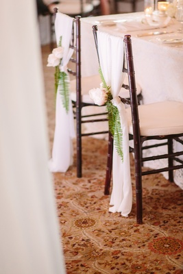 bride and groom seat marker, all-white décor flowers on bride and groom's chairs