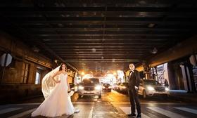 bride in essence of australia wedding dress, groom in bonobos tux, standing in crosswalk in Chicago
