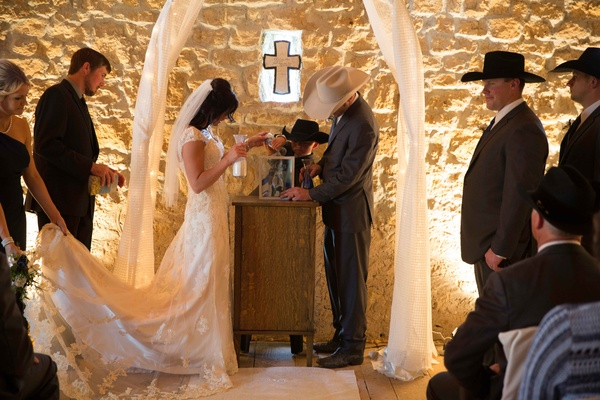 Bride and groom at altar with cross doing sand ceremony tradition