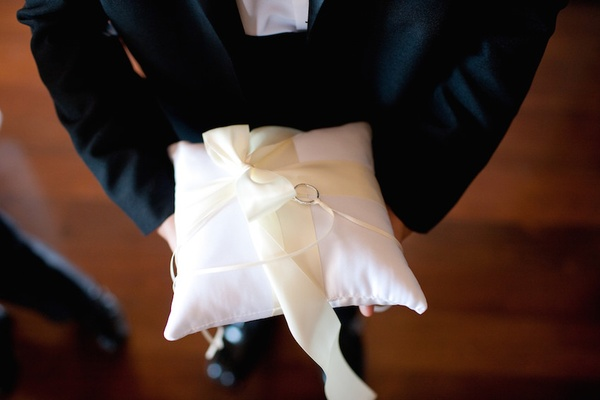 Ring bearer carrying wedding bands on plush pillow