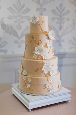 four layer wedding cake round tiers buttercream white sugar flowers gold vines blush frosting