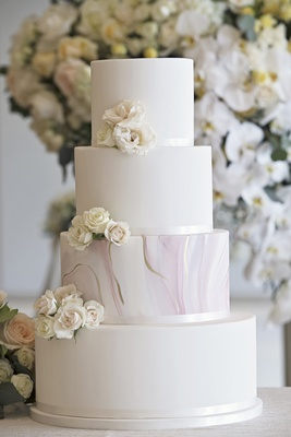 Minimalist wedding cake with blush and gold marble tier, fresh white flowers as accent