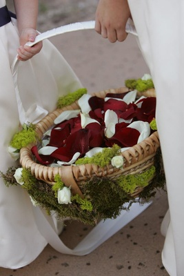 Moss-covered tan basket filled with petals