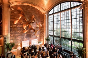 Wedding cocktail hour guests in lobby of venue tall glass window new york city venue