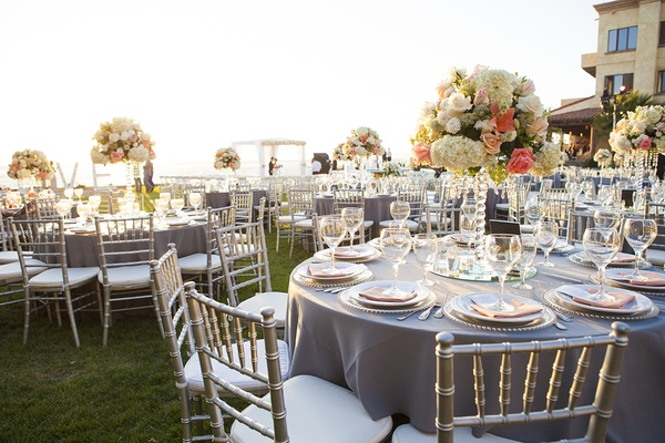 Wedding reception on grass lawn in Mexico with grey linens, white and coral centerpieces, crystals