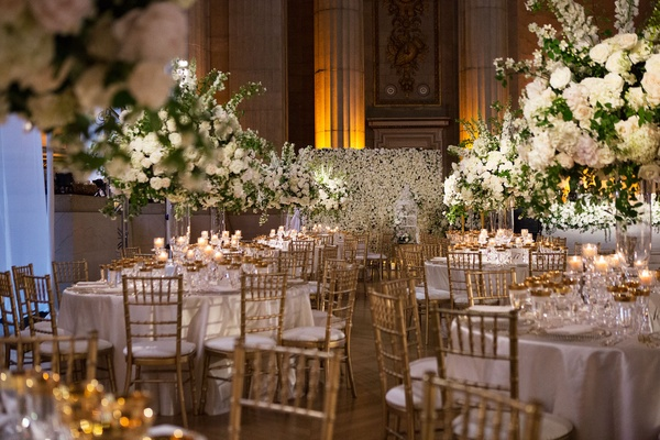 Wedding reception flower wall round tables gold chairs tall centerpiece high flowers white greenery