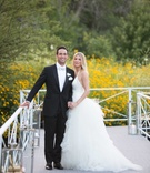 Bride in halter top Vera Wang wedding dress and groom in tuxedo with white bow tie in backyard