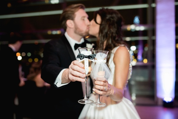 Bride and groom kiss while holding out champagne glasses decorated with bow tie and tulle his hers