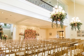 Wedding ceremony in grand hall of club gold chairs flower wall flower chandeliers