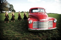 Vintage red truck takes bridesmaids to wedding ceremony