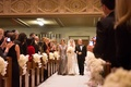 Bride in a lace Monique Lhuillier gown is walked down the aisle by her parents