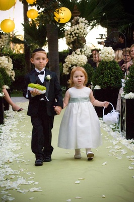 Ring bearer and flower girl walk down garden ceremony aisle