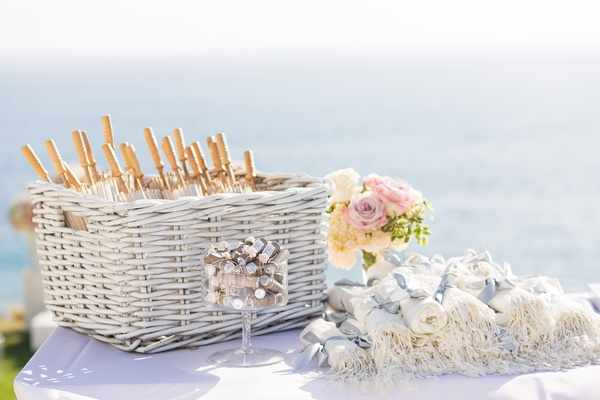 outdoor wedding ceremony preparations with parasols and pashminas for guests