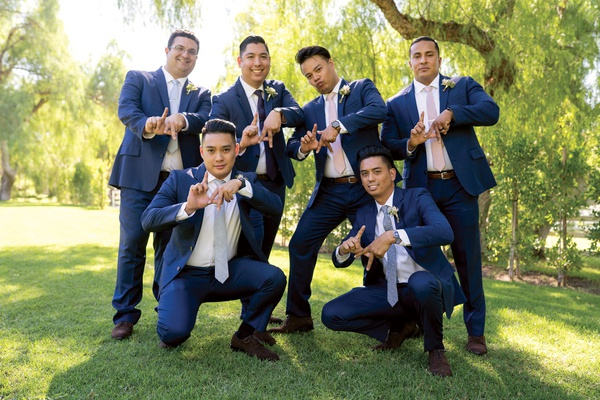 groomsmen in navy suits and different color ties doing LA symbol with their hands