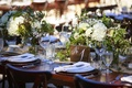 Rustic outdoor wedding reception table with wood block table number, white roses, hydrangeas