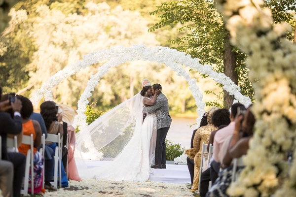 bride and groom kiss under white flower arches outdoor garden ceremony ghana royalty africa wedding