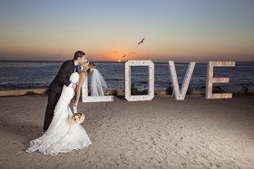 Bride in strapless wedding dress dipped by groom in tuxedo kissing at sunset on beach in Mexico